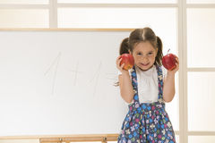Children education concept. Cute toddler playing teacher role game. Little girl learning to count with apples, indoor shot Stock Images