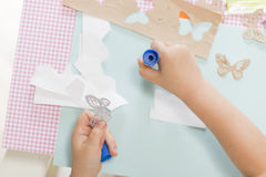 Children education concept. Little child hands sticking butterfly paper on the art lesson class. Kids crafts. Learn Study Education School Knowledge Concept Royalty Free Stock Photography
