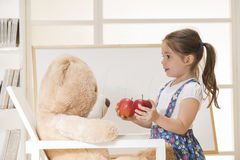 Children education concept. Little girl teaching her toy bear friend to count with apples, indoor shot. Cute toddler playing teacher role game. Little lovely Royalty Free Stock Image