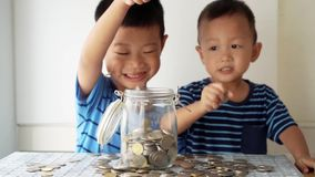 Children education concept with money jar. Slow motion children drops coin money into glass jar, financial concept stock footage