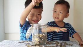 Children education concept with money jar. Slow motion children drops coin money into glass jar, financial concept stock video