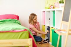 Girl with schoolbag at home. Children, education and people concept - happy girl putting schoolbag to shelf at home Stock Photography