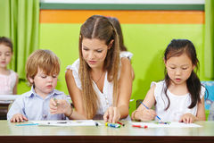 Children and educator painting. In kindergarten with brushes on paper Stock Image