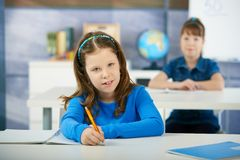 Children in elementary school classroom. Schoolgirls sitting at desk in primary school classroom. Elementary age children Royalty Free Stock Photo