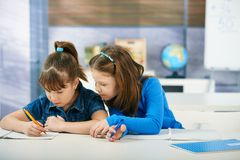 Children in elementary school classroom. Children sitting at desk working together in primary school classroom.  Elementary age children Stock Images