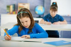 Children in elementary school classroom. Schoolgirls sitting at desk in primary school classroom. Elementary age children Stock Photos