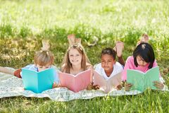 Children of elementary school learn to read. Group of primary school children learning to read in the open air stock photo