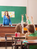 Children in elementary school are raised hand in clasroom Royalty Free Stock Photo