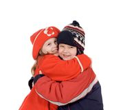 Children embrace. In winter clothes on a white background Royalty Free Stock Photography
