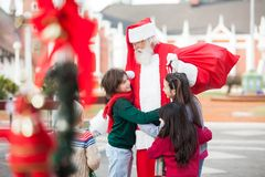 Children Embracing Santa Claus Royalty Free Stock Photos