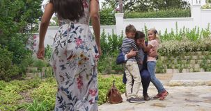 Children embracing their father after returning home 4k. Front view of Caucasian children embracing their father after returning home. They are smiling 4k stock footage