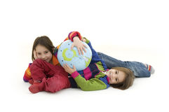 Children embracing world globe. Two children embracing a world globe isolated on white Stock Image