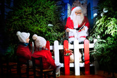 Children enchanted by stories of a Santa Claus Royalty Free Stock Photography