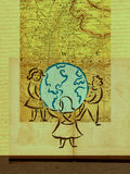 Children encircling a globe with a map Royalty Free Stock Image