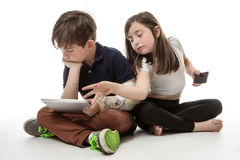 Children engrossed in technology. Two children sitting next to each other whilst playing with a mobile phone and a tablet computer Royalty Free Stock Photo