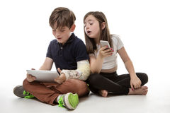 Children engrossed in technology. A young girl and boy playing on their tablet computer and mobile phone Stock Photos