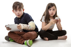 Children engrossed in technology. A young girl and boy playing on their tablet computer and mobile phone Stock Photography