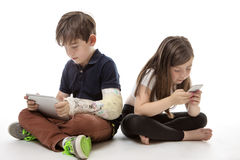 Children engrossed in technology. A young girl and boy playing on their tablet computer and mobile phone Royalty Free Stock Photos