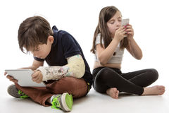 Children engrossed in technology. A young girl and boy playing on their tablet computer and mobile phone Stock Images