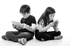 Children engrossed in technology. A young girl and boy playing on their tablet computer and mobile phone Stock Image