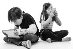 Children engrossed in technology. A young girl and boy playing on their tablet computer and mobile phone Royalty Free Stock Photo
