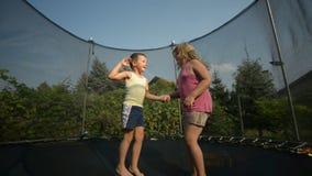 Children enjoy jumping on trampoline stock footage