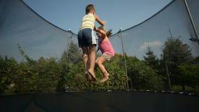 Children enjoy jumping on trampoline stock video footage