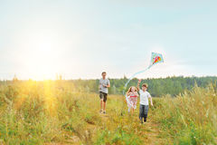 Children enjoy playing with a flying kite in meadow on sunny day Stock Photos