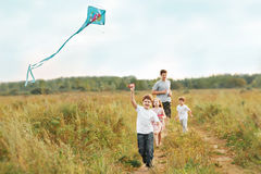 Children Enjoy Playing With A Flying Kite. Stock Photo