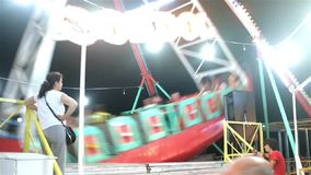 Children enjoy a ride in amusement park stock video footage