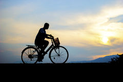Children enjoy ride bicycle during sunset. Royalty Free Stock Photo