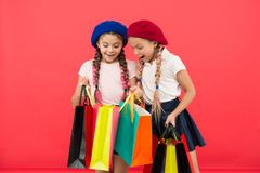 Children enjoy shopping red background. Visiting clothing mall. Discount and sale concept. Kids cute girls hold shopping. Bags. Shopping discount season royalty free stock photo