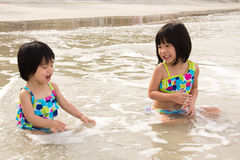 Children enjoy waves on beach Royalty Free Stock Photography