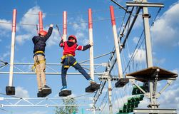 Children enjoying activity in a climbing adventure park on a sunny day. Safe climbing extreme sport with helmet and carabiner royalty free stock photo