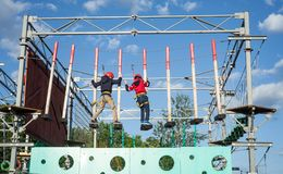 Children enjoying activity in a climbing adventure park on a sunny day. Safe climbing extreme sport with helmet and carabiner stock photo