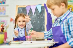 Children Enjoying Art Class of Development School. Portrait of adorable little girl painting pictures enjoying art class in pre school working together with royalty free stock photography