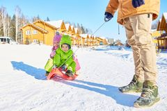 Children enjoying sleigh ride. Father pulling sled with happy little boy and girl along snowy road in resort area  on beautiful winter afternoon Royalty Free Stock Photo