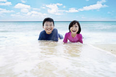 Children enjoying their vacation on the beach. Photo of two happy children lying on beach and playing with waves on summer vacation Royalty Free Stock Image