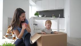Children entertainment, little cute baby in cardboard box playing hide-and-seek with mom and claps hand in room. Children entertainment, little cute baby in stock footage