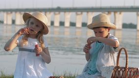 Children entertainment, sweet lovely child boy and girl in straw hats blow bubbles during picnic in nature. Near river stock footage