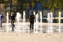 Children examine and test the new fountain. royalty free stock photography