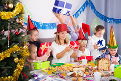 Children exchanging Christmas gifts. Children handing presents to each other during Christmas dinner royalty free stock images