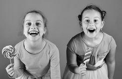 Children with excited faces pose with candies on green background. Sisters with round and long shaped lollipops. Girls eat big colorful sweet caramels royalty free stock photos