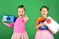 Children with excited faces pose with presents on green background. Xmas holidays concept. Girls open gifts for Christmas showing thumbs up. Sisters with royalty free stock image