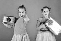 Children with excited faces pose with presents on green background. Xmas holidays concept. Girls open gifts for Christmas showing thumbs up. Sisters with stock image