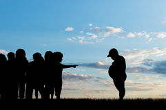 Children expel fat child. Children expel fat boy on background of sky. Concept of childhood obesity Stock Photos