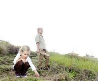 Children exploring. Brother and sister playing outdoors, exploring with wooden sword and being kids together royalty free stock photo