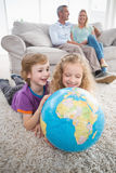 Children exploring globe while parents sitting on sofa Royalty Free Stock Photo
