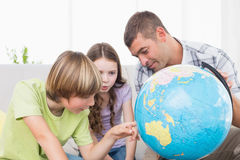 Children exploring globe while sitting with father Royalty Free Stock Photos