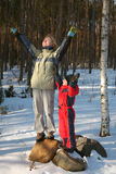 Children express happiness in winter scene. A young woman and young boy hold their arms up to the sky in an expression of joy in a winter scene royalty free stock photography